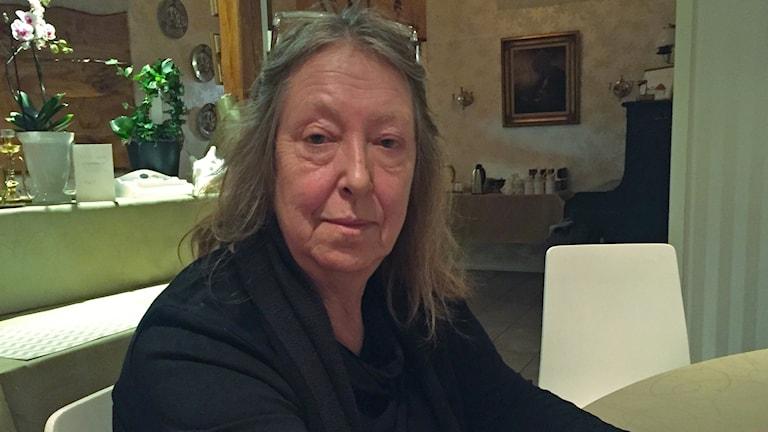 Kvinna sitter inomhus, iklädd svart tröja.