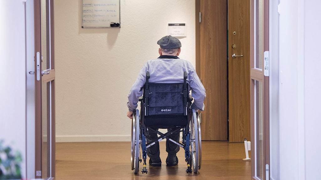 En person i rullstol rullar bortåt i bilden.