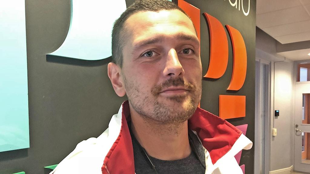 Adnan Dibrani framför Sveriges Radios logga.