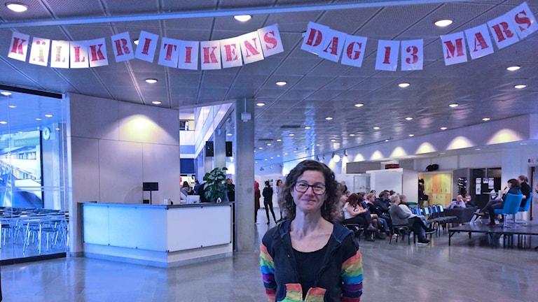 Lotta Eliasson står inne i en skollokal. Ovanför står i röda bokstäver Källkritikens dag 13 mars.