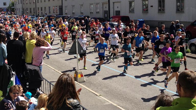 Människor springer ett stadslopp förbi åskådare.