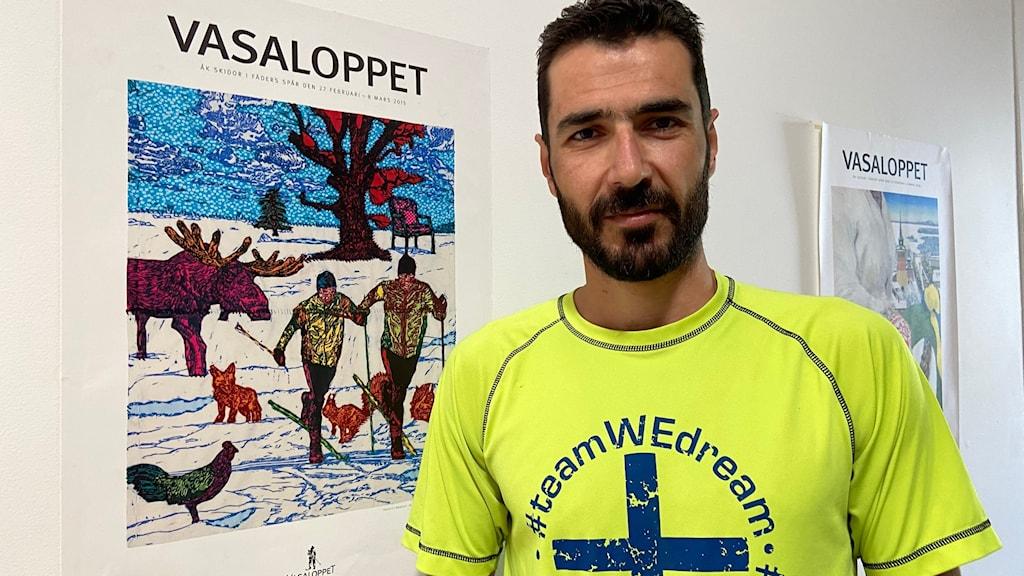 Man står bredvid historisk affisch från Vasaloppet.