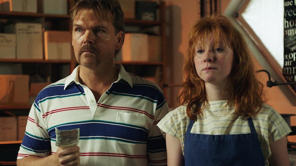 En man och en kvinna, klädda i 80-talskläder, står i vad som ser ut som en affär eller ett lager. De ser upprörda ut.