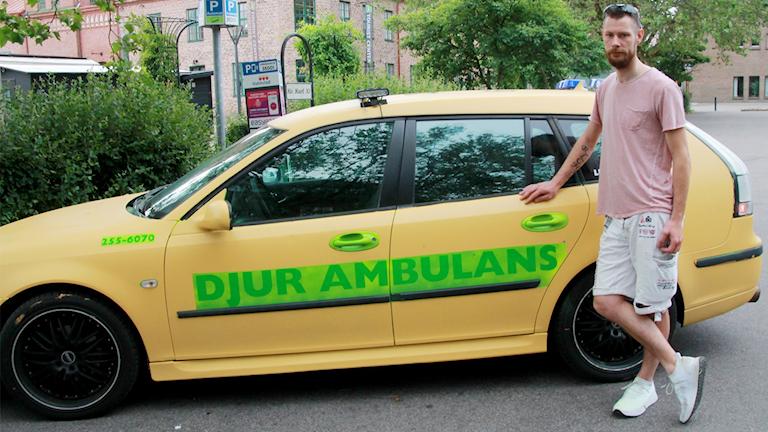Richard Larsen står framför en gul bil med texten Djurambulans