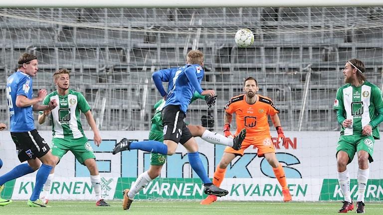 Fotbollsspelare i blå tröja nickar in en boll i mål.