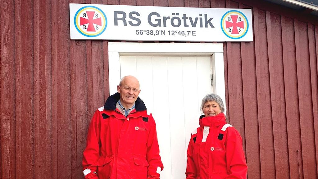 Man och kvinna i röda jackor Står framför röd byggnad med vit dörr