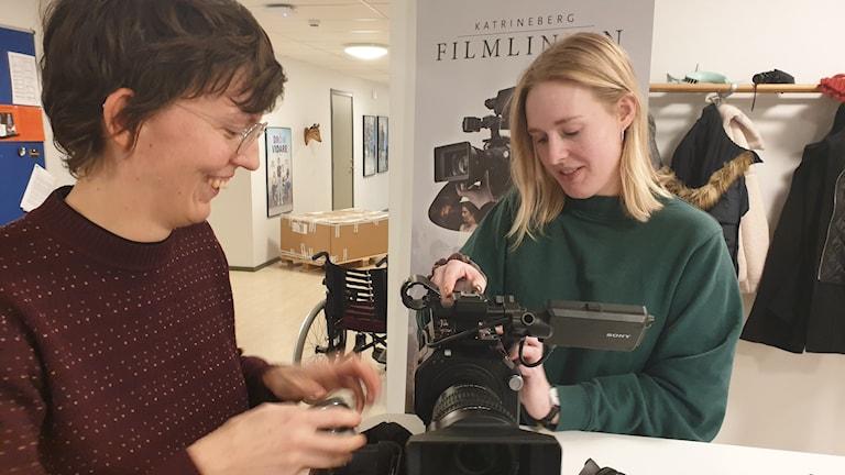 två kvinnor står vid ett bord och pillar på en filmkamera.