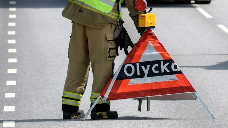 """Blåljuspersonal ställer ut en tillfällig skylt på en väg. På skylten står det """"olycka"""". Foto. Johan Nilsson/TT."""