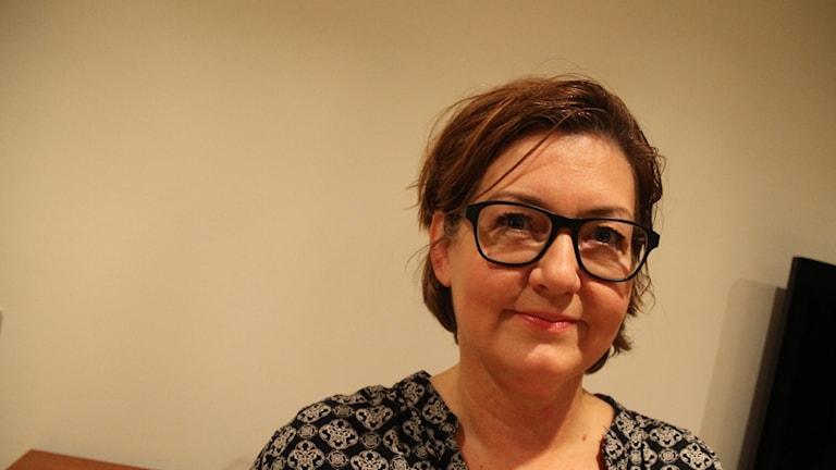 Eva-Lotta Olofsson med ljus tapet i bakgrunden