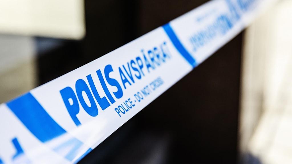 Blåvita polisavspärrningsband tvärs över bilden.