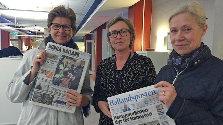 Tre kvinnor står inomhus, två håller upp varsin tidning framför sig.