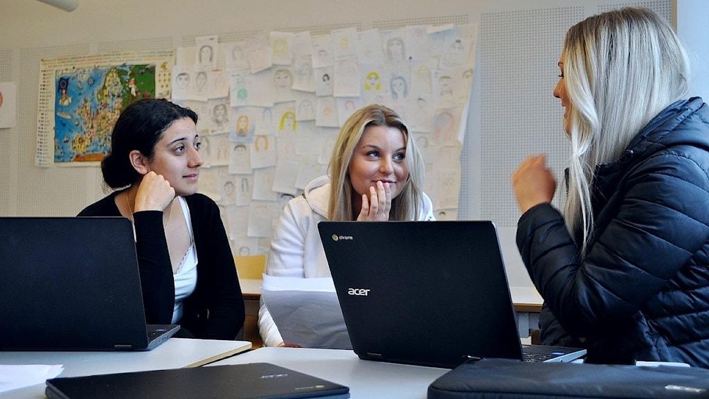 Saya Solhammar, Olivia Kristenson och Alexandra Carlsson sitter och diskuterar vid skolbänken.
