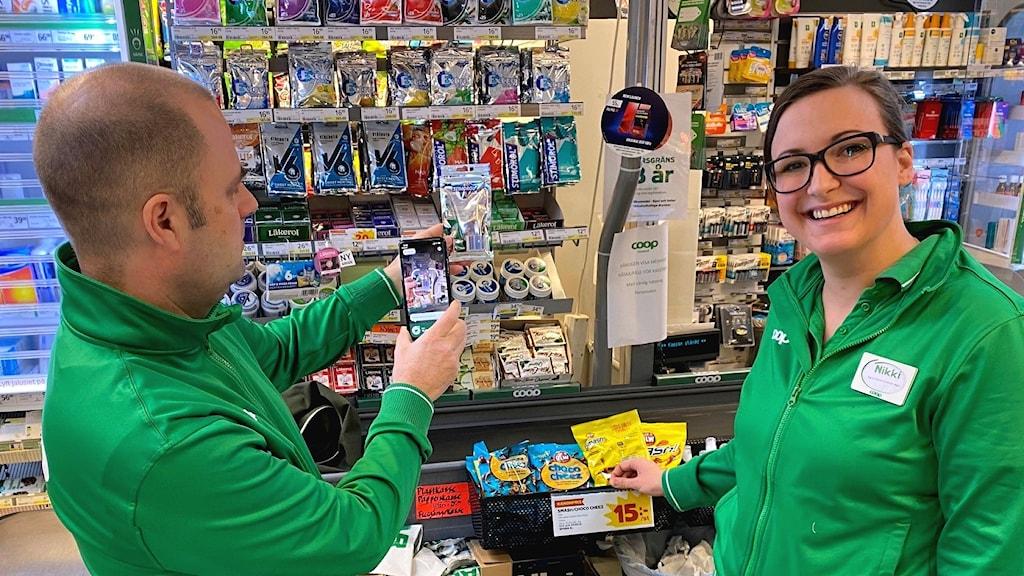Två personer, butikspersonal, i gröna tröjor i en livsmedelsbutik.
