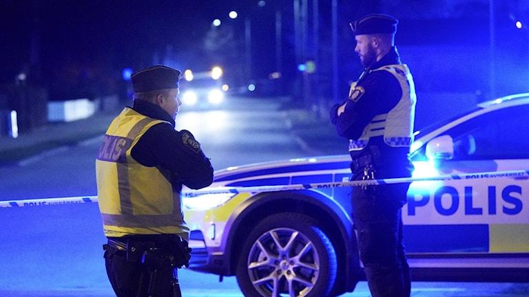 Två poliser i reflexvästar står vända mot varandra på en gata. Det är mörkt och en polisbils står parkerad i bakgrunden.