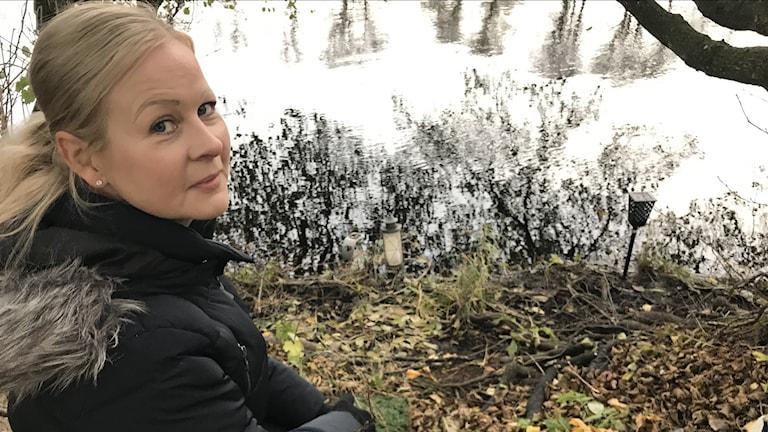 Kvinna sitter vid minnesplats. Omgivningen består av skog, gräs och vatten.