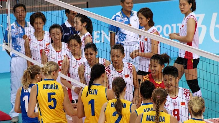 Landslagsklädda volleybollspelare står vid nätet.