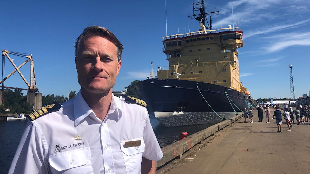 Kapten Karl Herlin framför den gula och blåa isbrytaren Atle.