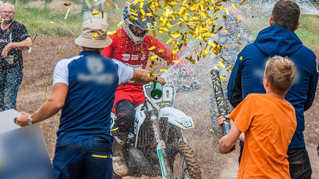 En man som kör motocross firas med bubbel och konfetti vid mål.