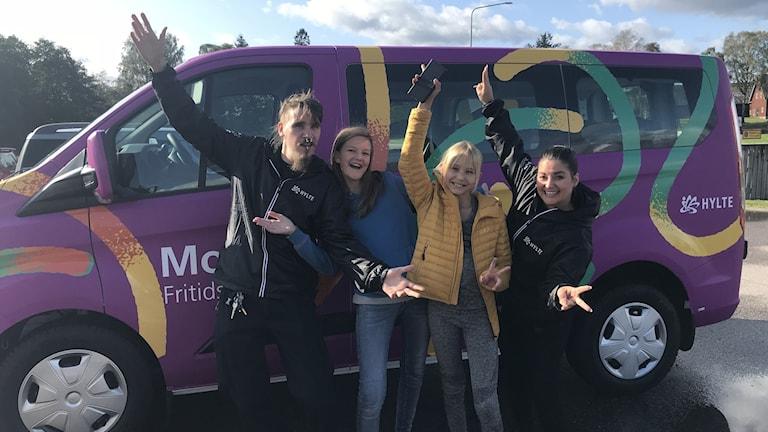 Fyra personer är glada och står framför en lila minibuss.