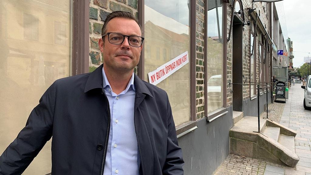 Kommunrådet i Halmstad moderaten Jonas Bergman står framför en tom affärslokal.