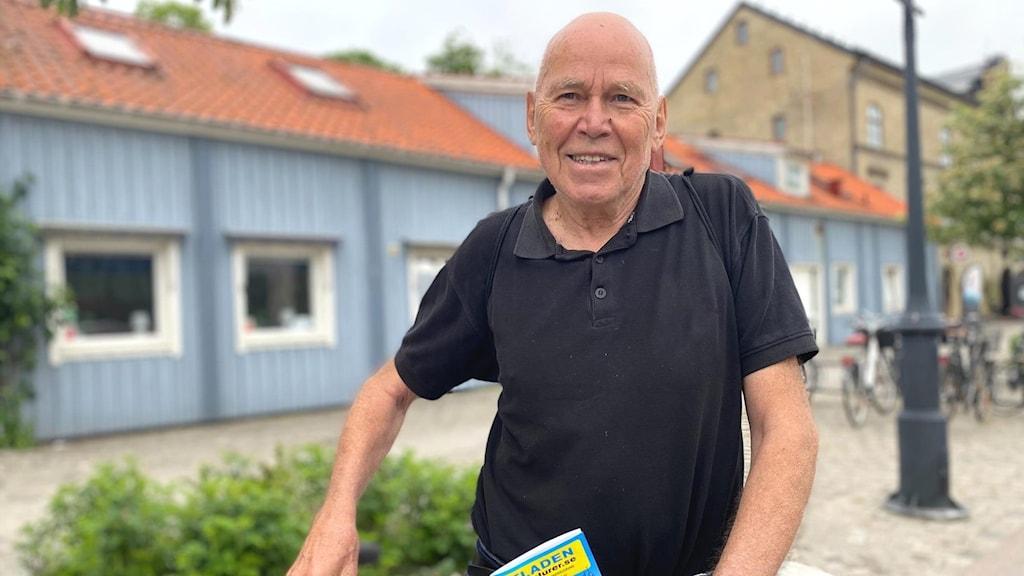 En äldre man fotad framifrån, leendes mot kameran. Iklädd svart t-shirt och i bakgrunden syns blå hus.