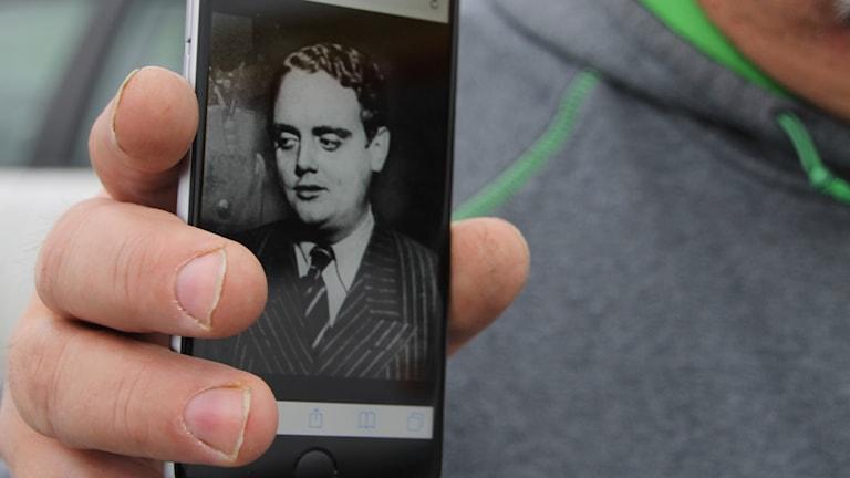 Lars-Rune Jätbrink håller upp mobilbilden på sin farfar Johnny Bode.