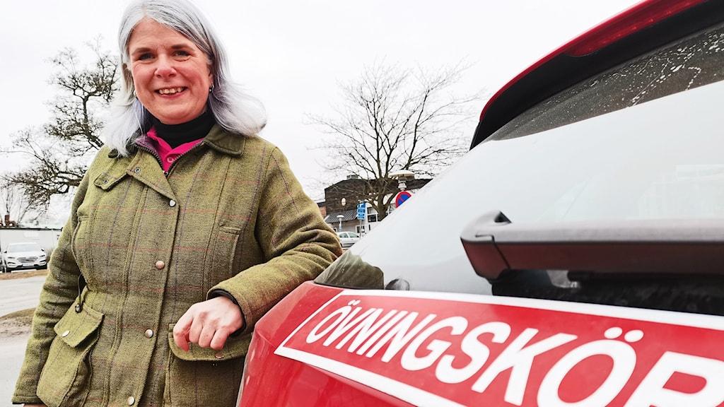 En kvinna står vid en bil med en skylt där det står Övningskör.