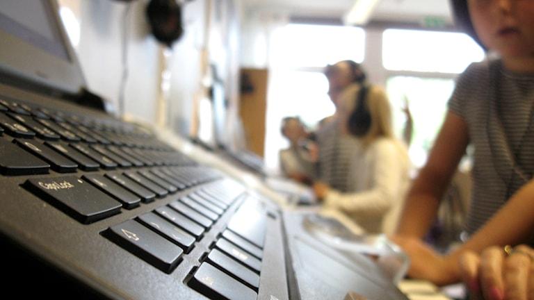 Förstaklasselever sitter vid datorer och skriver och hör ljud i sina hörlurar, i ett klassrum i Kungsbacka.