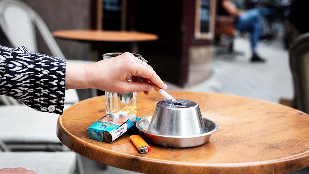En person fimpar cigarett i en askkopp på ett kafébord.