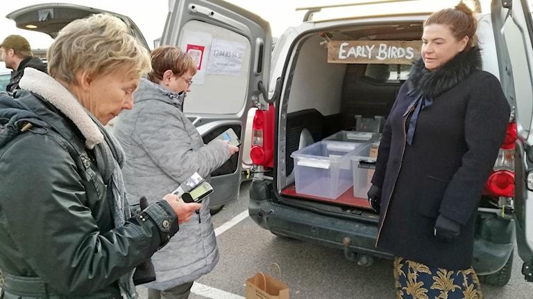 Två kvinnor betalar med mobiltelefon till en tredje kvinna som säljer varor vid en rekoring i Varberg.