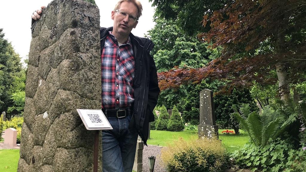 Man står vid gravsten där en skylt med QR-kod syns i förgrunden.