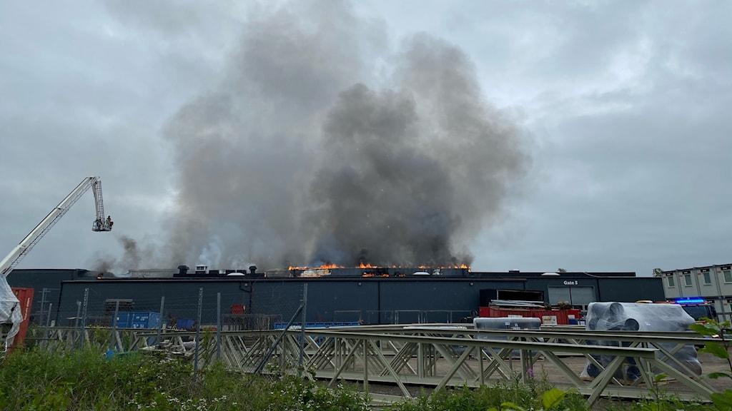 Svart brandrök på en grå himmel. Unders i bild syns ett brinnande tak på en industribyggnad.