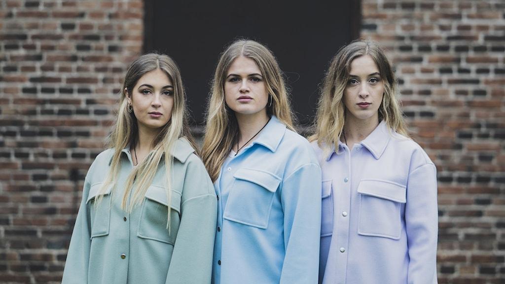 Tre tjejer i pastellfärger står framför en stenmur