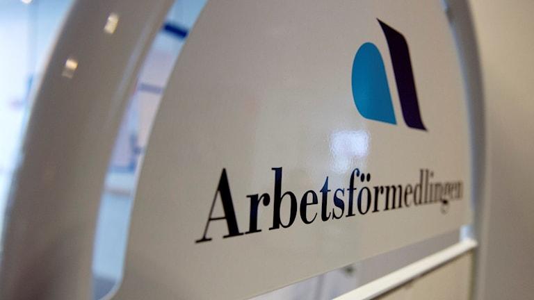 """En vit skylt med Arbetsförmedlingens logotyp och texten """"Arbetsförmedlingen"""". Foto: Jessica Gow/TT."""