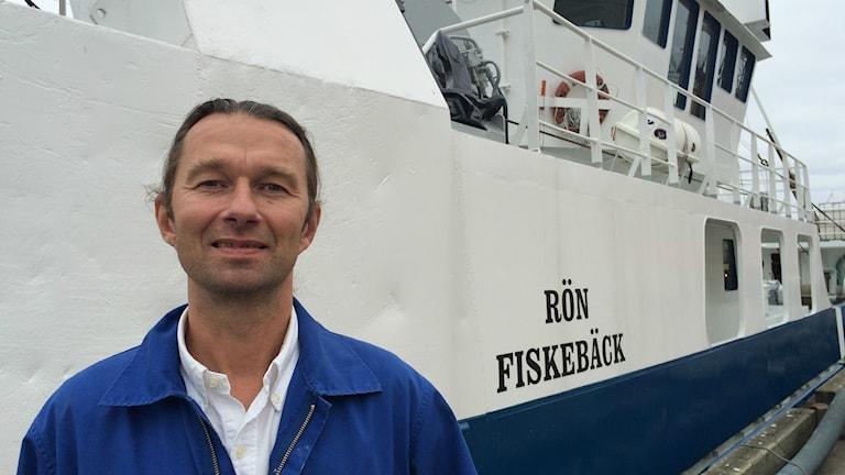 Sillproducenten Martin Kuhlin står framför trålaren Rön Fiskebäck. Foto: Sveriges Radio