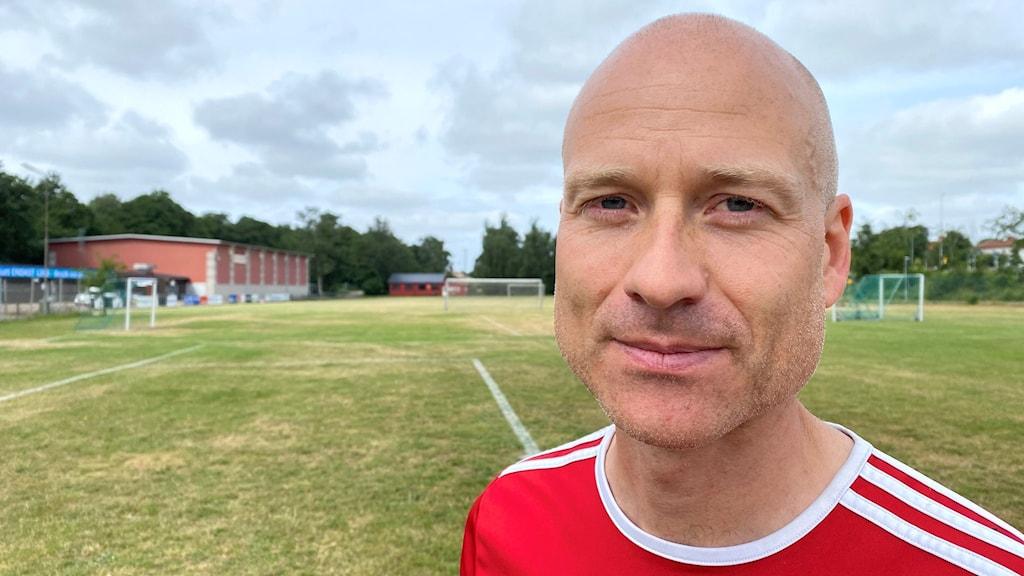 En man utan hår på huvudet, klädd i rödvit tröja. Han står på en fotbollsplan där gräset delvis är gult och torrt.