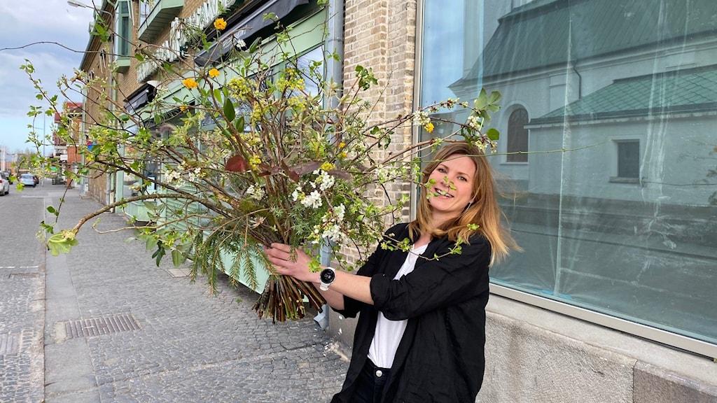 En kvinna står utomhus på en trottoar. Hon har blont hår och en vit t-T-shirt med en svart kofta. I handen håller hon en stor bukett med blommor och kvistar från den svenska naturen.