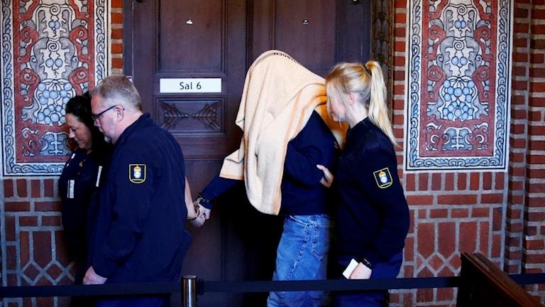 Misstänkt leds av polis i Borås tingsrätt.
