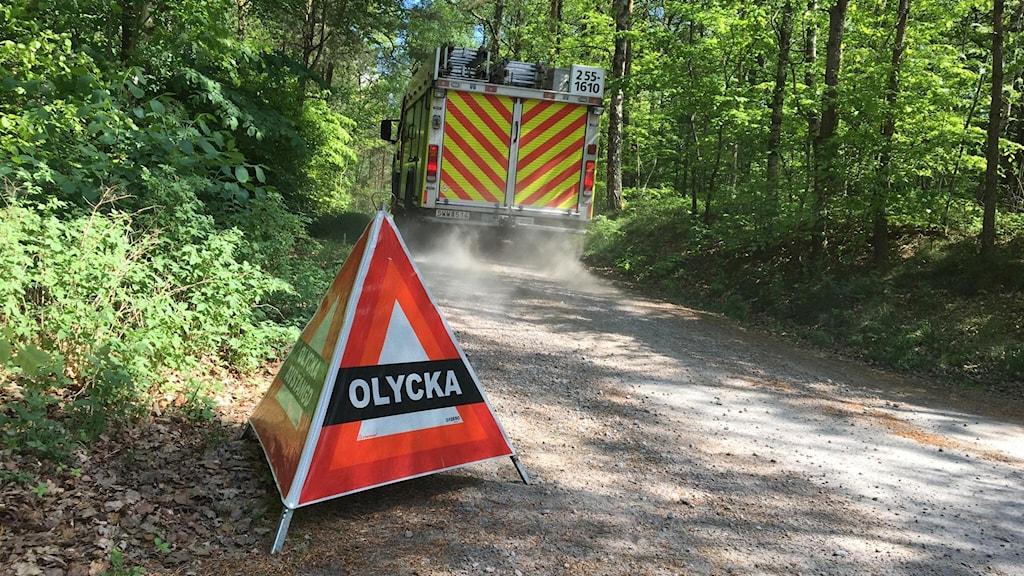 Skylt där det står olycka och en brandbil i en lövskog.