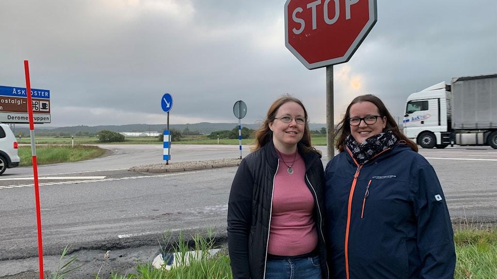 Två kvinnor står vid en stop-skylt vid en korsning. De ler och tittar in i kameran.