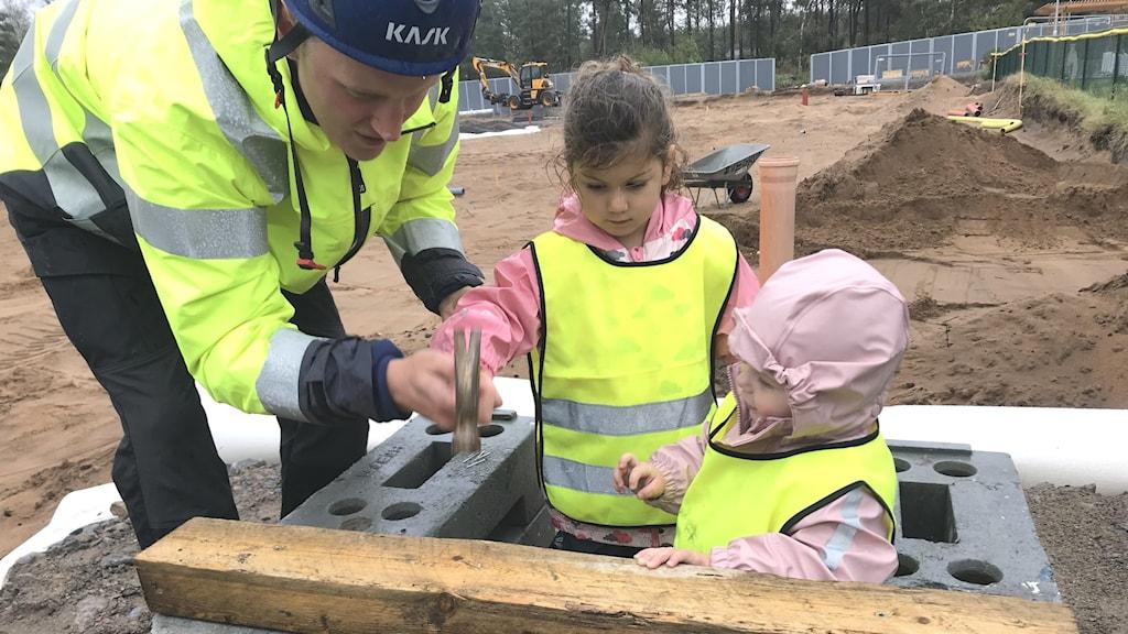 En byggarbetare och två förskolebarn står på en byggarbetsplats. Framför sig har de en träplanka. Byggarbetaren, till vänster, hjälper barnet i mitten, Léa, att spika med en hammare. Till höger om henne står barnet Bailey. Alla har på sig gula skyddsvästar.