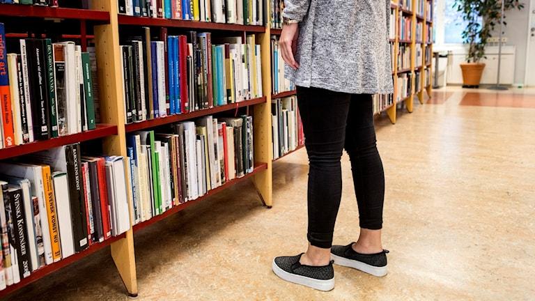 Person står framför en bibliotekshylla full med böcker. Foto: Christine Olsson/TT.