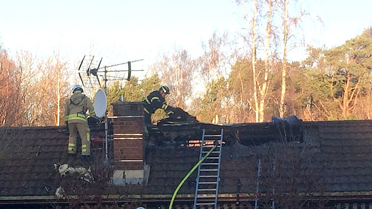 Räddningstjänstpersonal på taket på ett hus där det brinner. Foto: Muhamed Ferhatovic/Sveriges Radio.