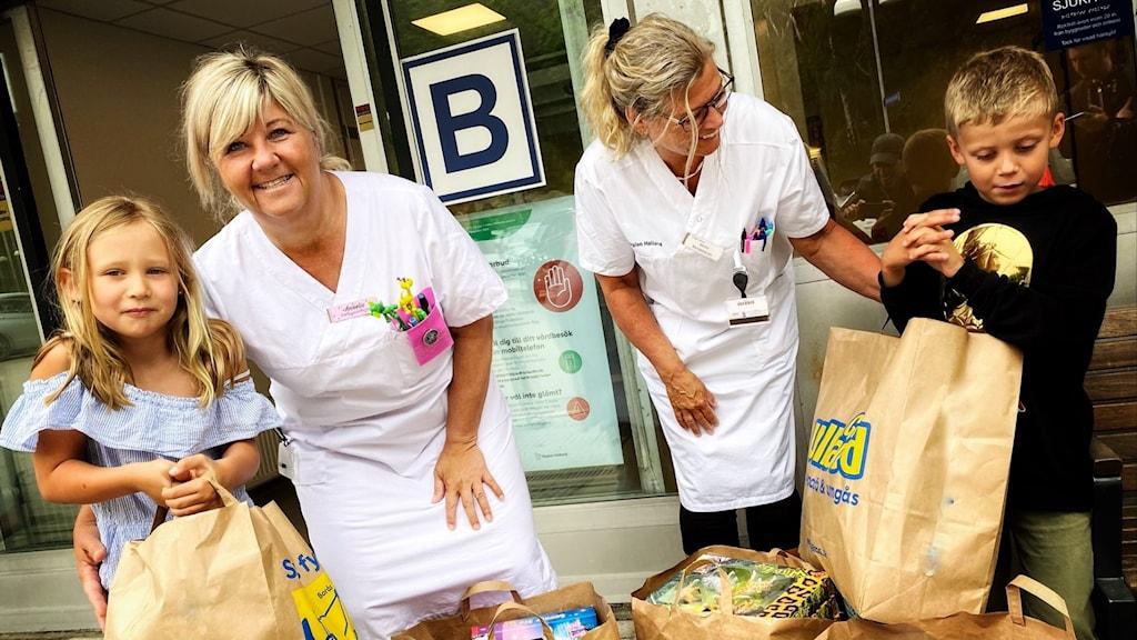Två barn överlämnar presenter i stora kassor till två barnsjuksköterskor i Kungsbacka.