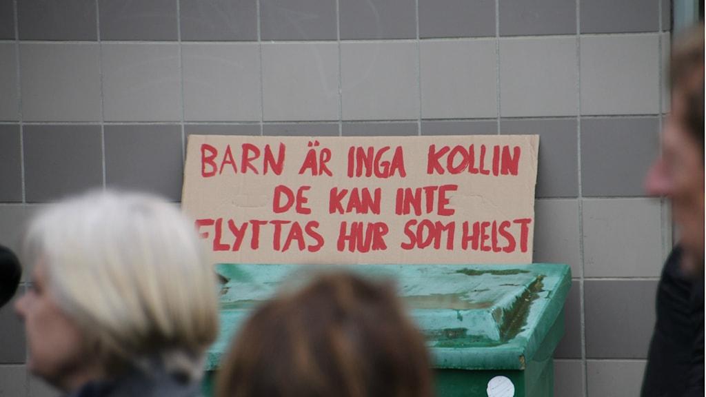 En av skyltarna bland åhörarna vid manifestationen och Röda tråden marschen.