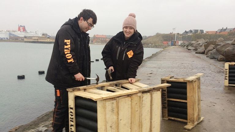 Niklas Medefelt och Elin Eriksson, iklädda svarta jackor står med varsin hammare i handen framför en trälåda gjort av tydligt synliga brädor och hamrar. Inuti lådan syns svarta rör där bomberna stoppas. Elin tittar upp mot kameran och ler medan Niklas tittar nedåt på lådan.