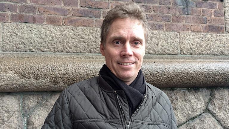 Jörgen Persson står framför en vägg utomhus.