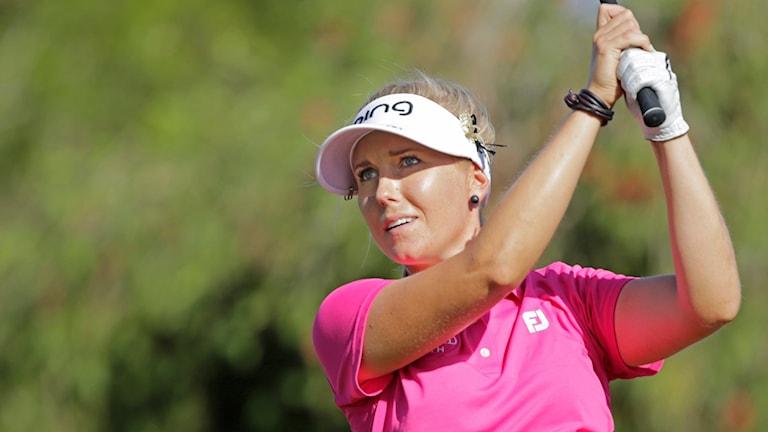 Elin Arvidsson, iklädd rosa t-shirt och vit keps spelar golf.