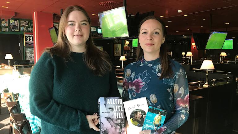 Bibliotekarierna Erika Johnsson och Annika Stattin står i en sportbar och håller i de tre böckerna.