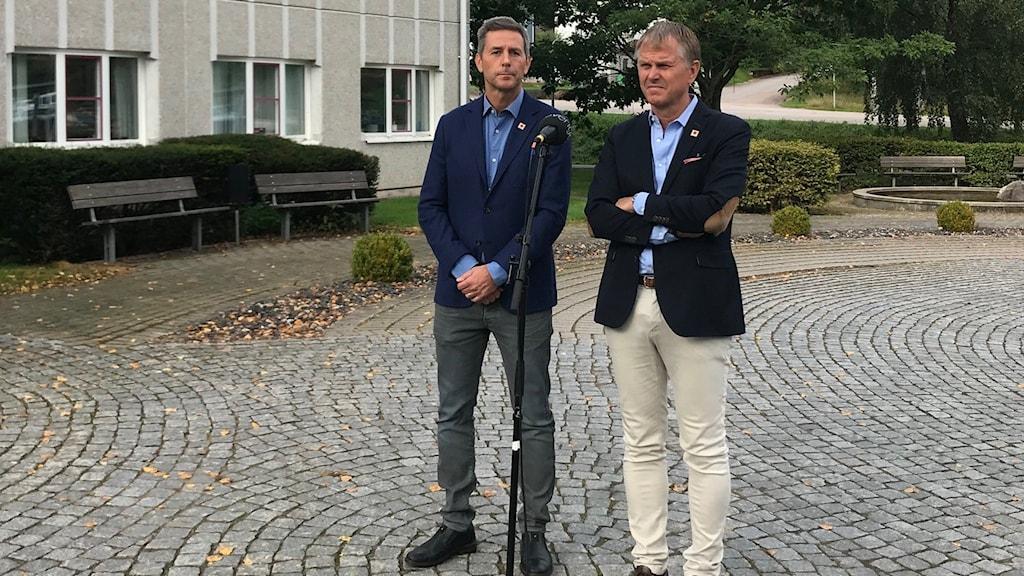 Två män står utomhus. Det står en mikrofon framför dem.